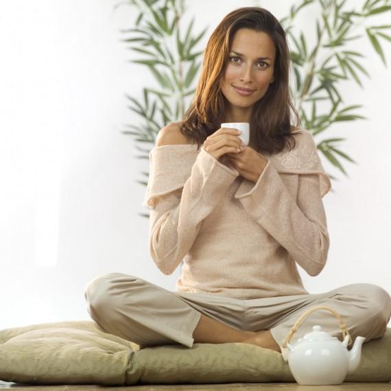 Девушка в позе лотоса с чаем