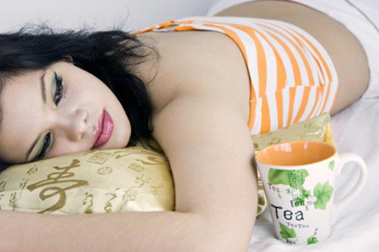 Девушка на подушке с чашкой чая